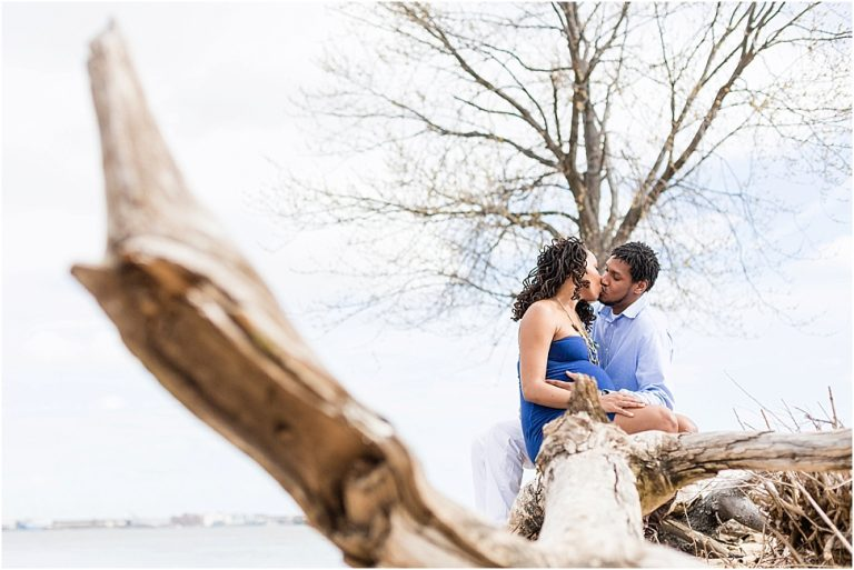 pregnant couple sitting on a piece of driftwood at river winds park