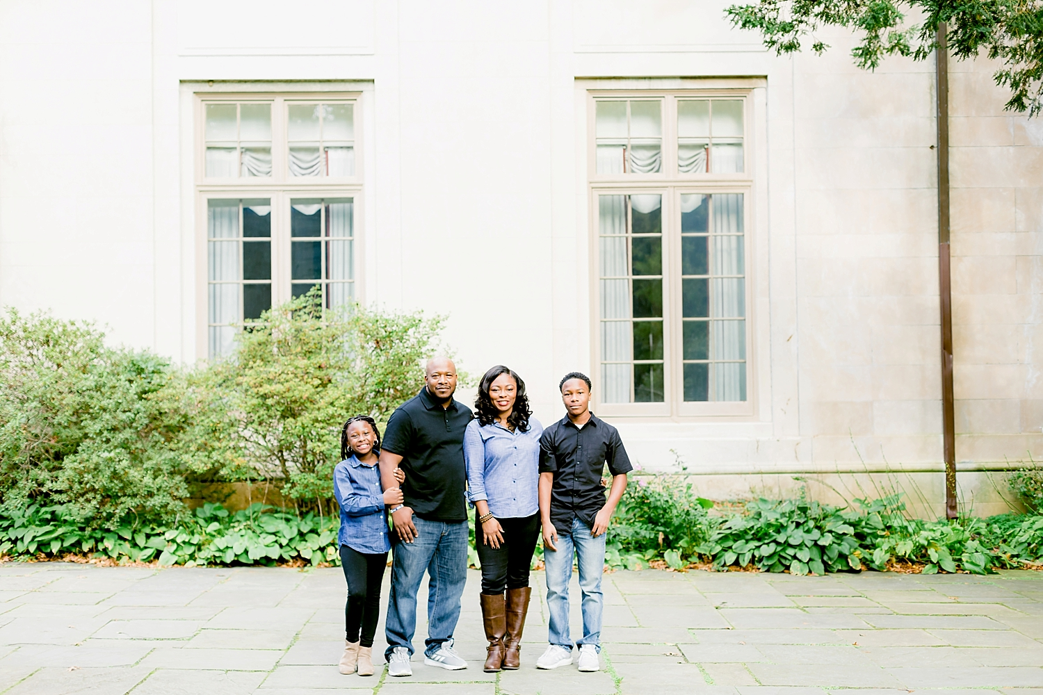 natural light photograph of family posing in denim and black outfits