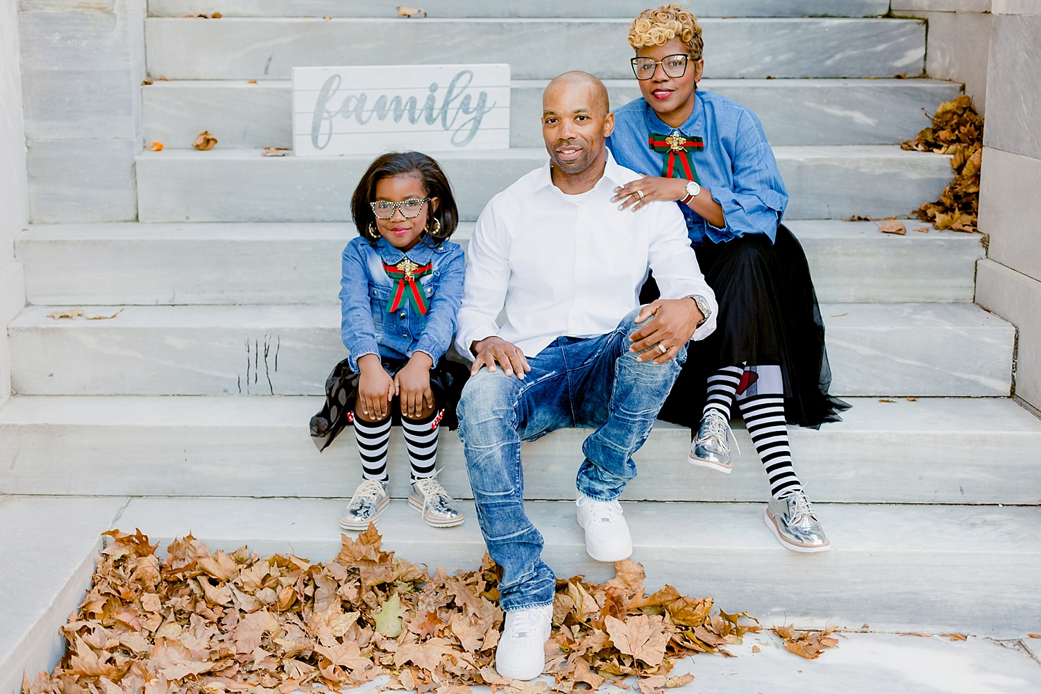 family sitting on steps of merchant exchange building for photo