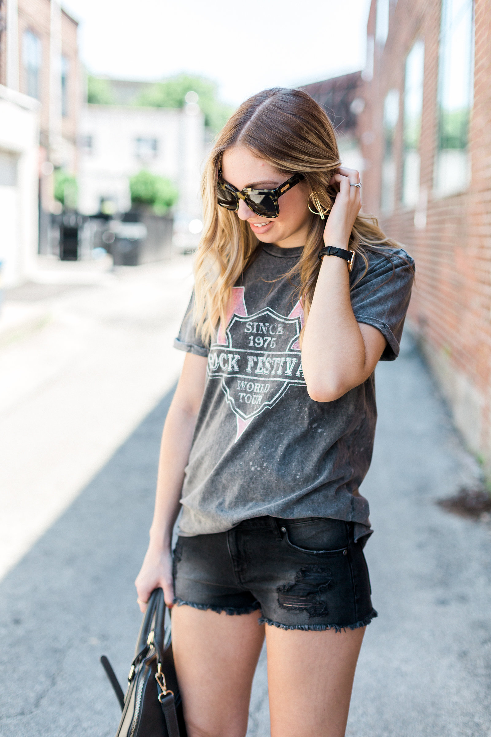 photo of blogger in denim shorts and graphic tee posing in Ardmore, PA shopping district