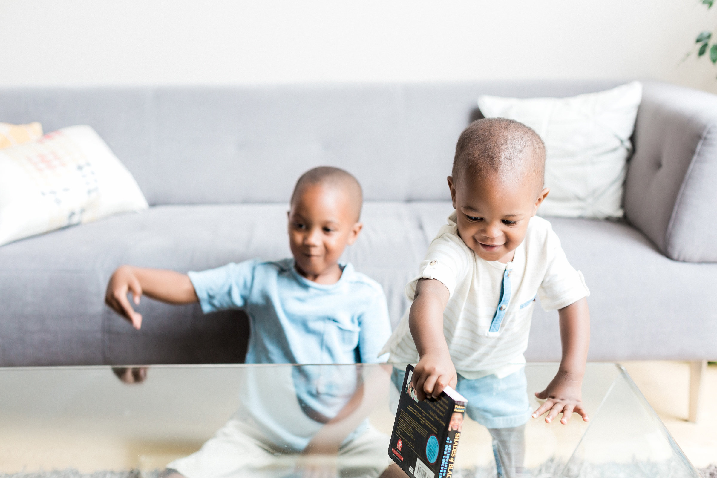 big brother plays with his baby brother in a modern living room