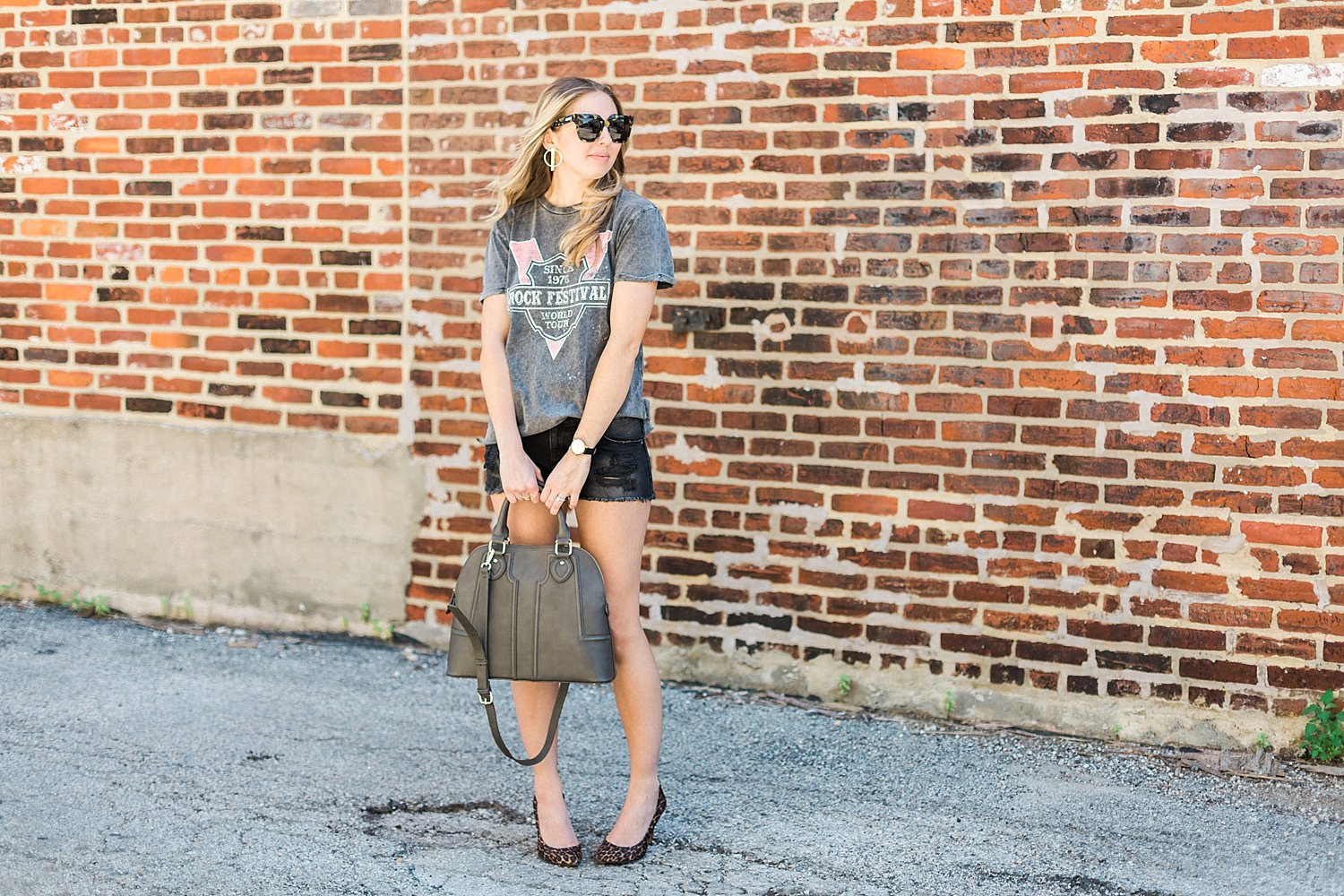 fashion blogger posing for branding photos in ripped denim shorts and a graphic tee