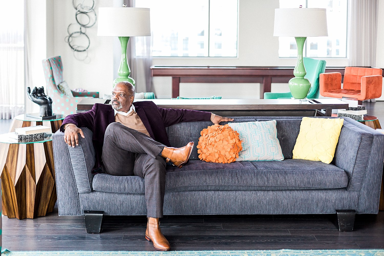 Casual lifestyle image of book writer sitting on a couch with colorful cushions