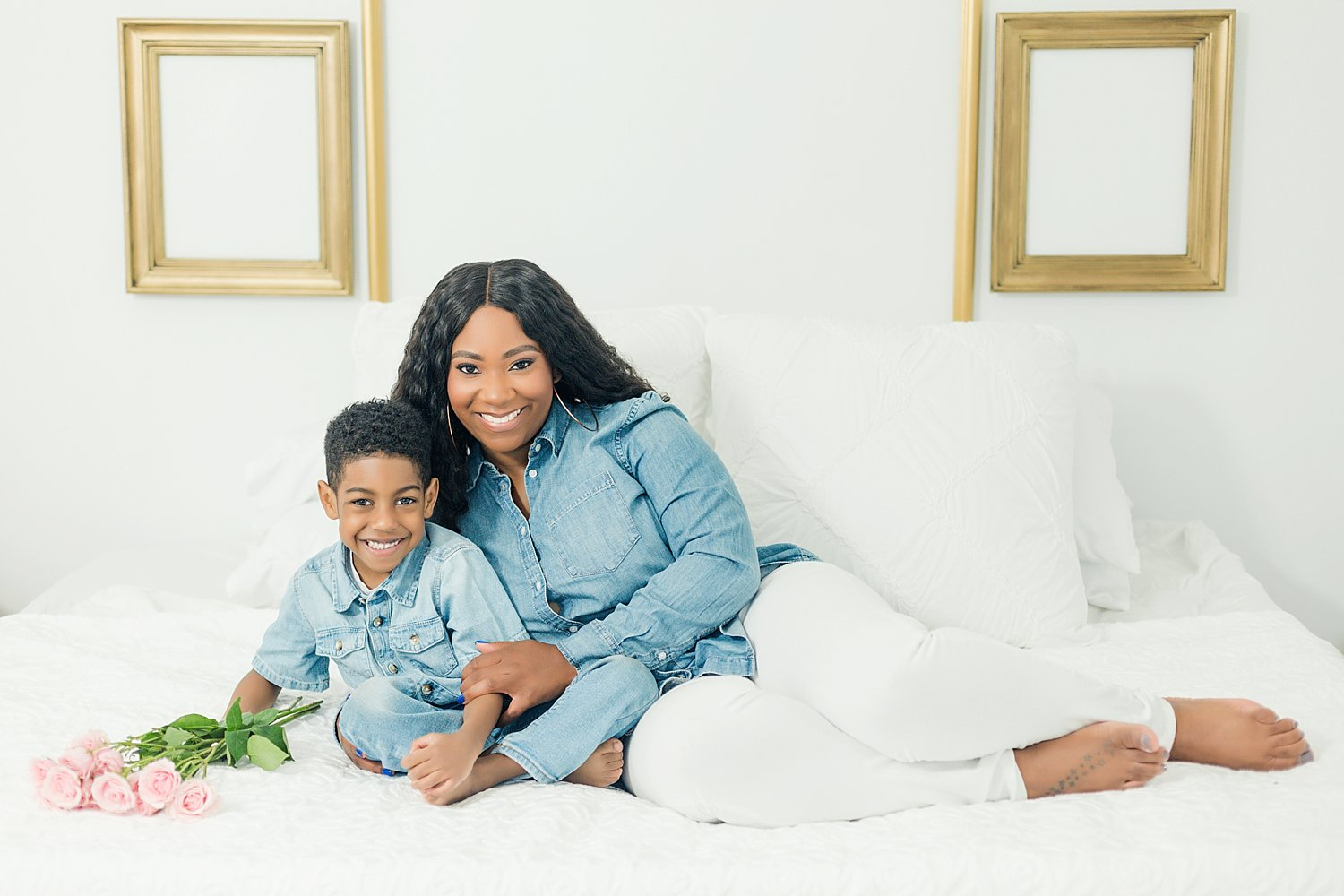 mother and son cuddling on white bed for studio portraits