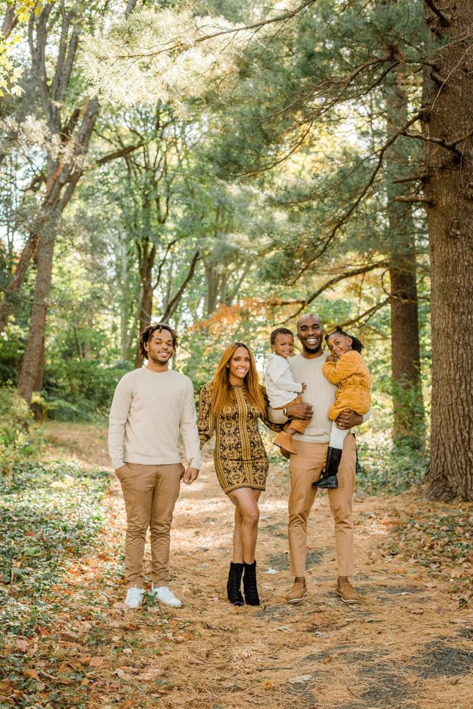 Family of five pose for portraits by Ann Blake Photography in Awbury Arboretum