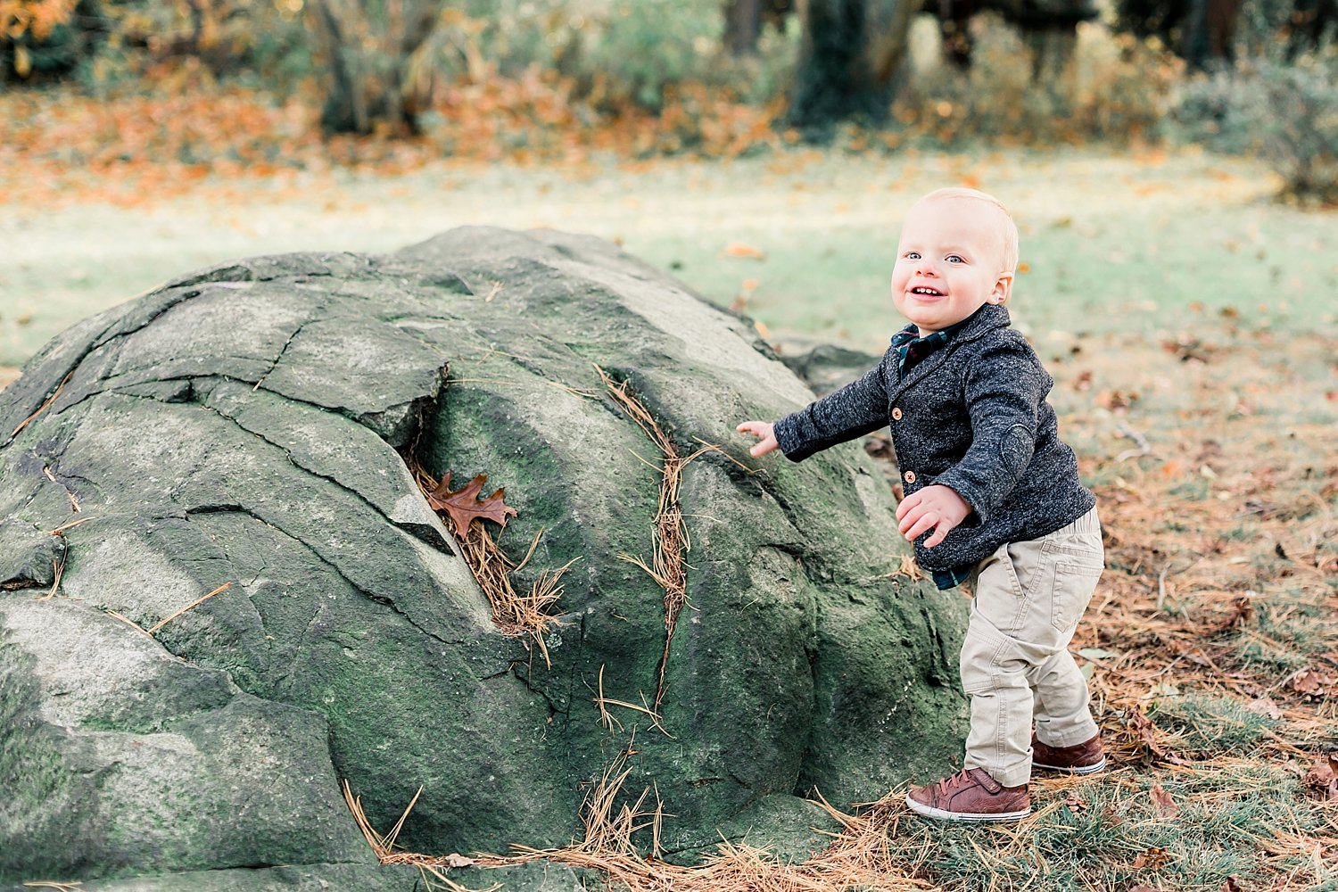 moving toddler takes a photo with a big rock in national park